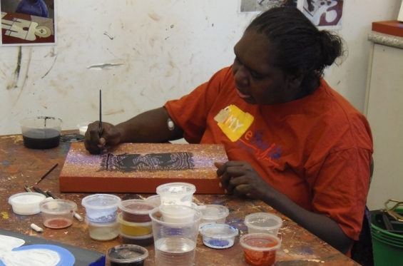 Artist Kirsty Burgu painting at the Mowanjum studio. © Chad Creighton & the Art Gallery of Western Australia 2013