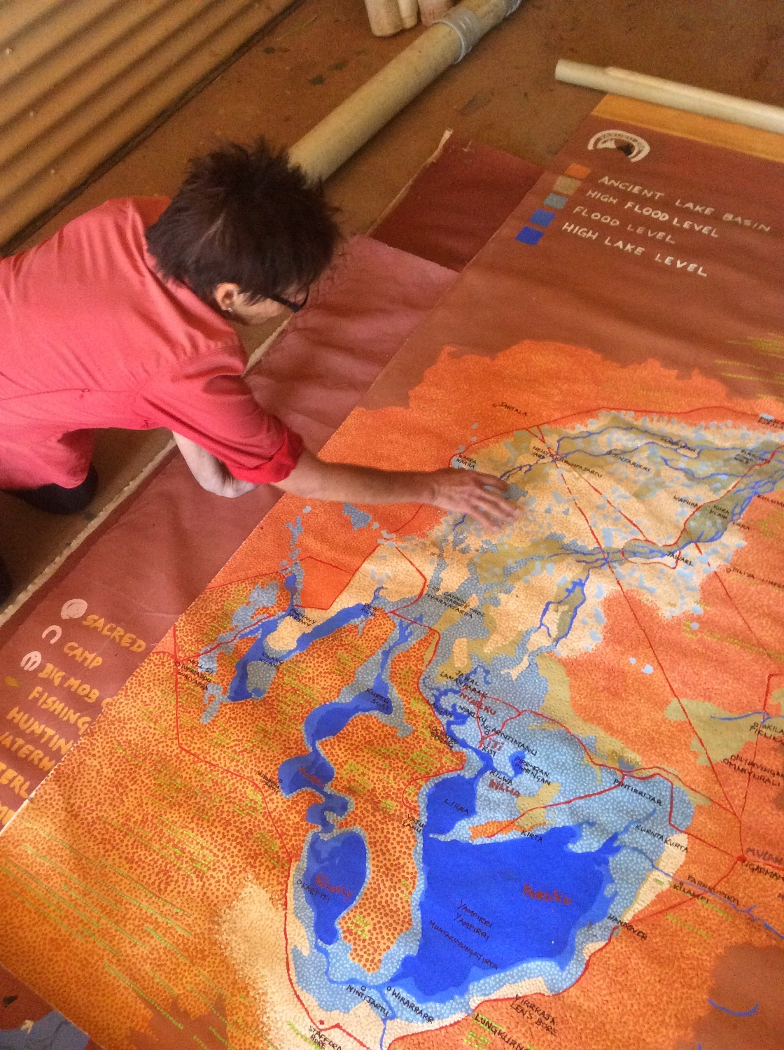 Kim Mahood unfurling the Lake Gregory water level, fire and cultural maps painted by Mulan artists. © AGWA 2016