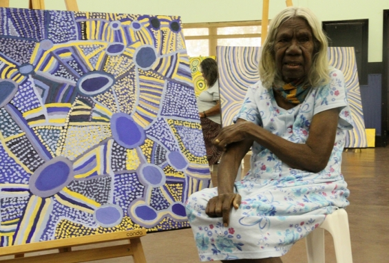 Lulu Trancollino with a couple of her paintings at Yarliyil Art Centre. © AGWA 2014