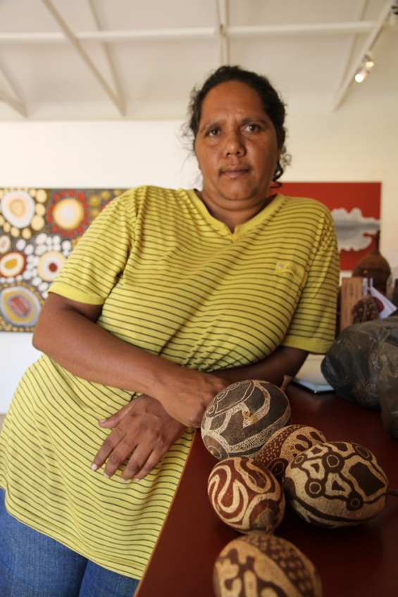 Margaret Beebe at Waringarri Aboriginal Arts with a selection of her engraved boab nuts. © AGWA 2014