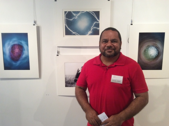 Artist and Visual Arts Leadership Program participant Michael Jalaru Torres standing with his artworks at the VALP exhibition opening in Kununurra, May 2016. © AGWA