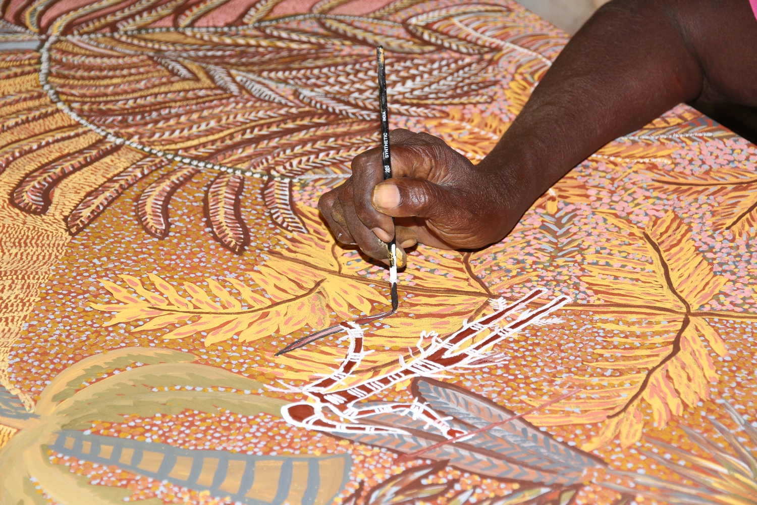 Artist Mary Puntji Clement painting at Kira Kiro Art Centre. © AGWA 2015