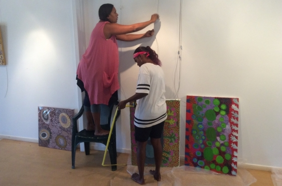 Lynley Nargoodah with Anthea Nargoodah hanging paintings for the 2016 Visual Arts Leadership Program exhibition in Kununurra. © Art Gallery of WA 2016