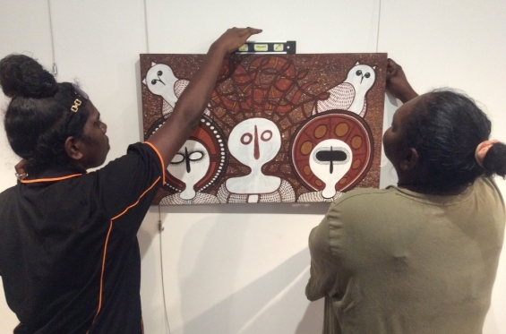 Cessa Bani hanging paintings during the 2016 workshop with fellow Visual Arts Leadership Program participant Kirsty Burgu. © Art Gallery of WA 2016