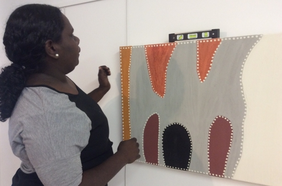 Marika Riley hanging paintings from Warmun Art Centre for the exhibition during the 2016 Visual Arts Leadership Program workshop. © Art Gallery of WA 2016