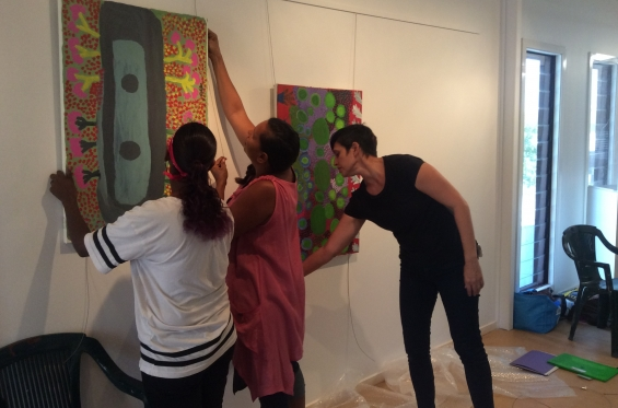 Carly Lane, AGWA Curator of Aboriginal and Torres Strait Islander Art guiding DRS 2016 Visual Arts Leadership Program participants Anthea and Lynley Nargoodah with hanging paintings from Mangkaja Arts Resource Agency for the inaugural VALP exhibition. © AGWA
