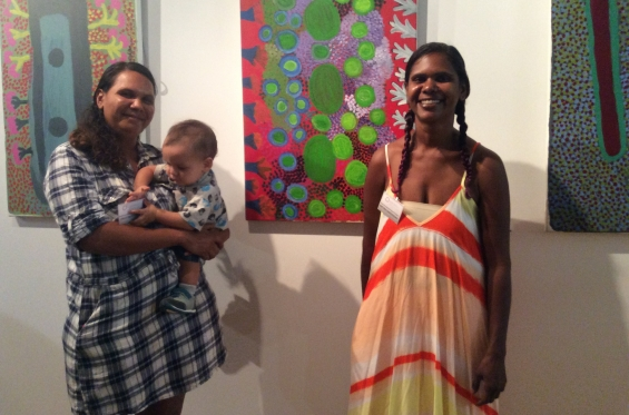 DRS 2016 Visual Arts Leadership Program participants Lynley and Anthea Nargoodah (and baby Wyatt) at the inaugural VALP exhibition opening standing with works from Mangkaja Arts Resource Agency that they helped curate and install. © AGWA