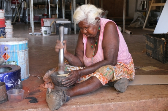 Warmun Art Centre artist Nancy Nodea grinding ochre pigments in the studio © AGWA 2014