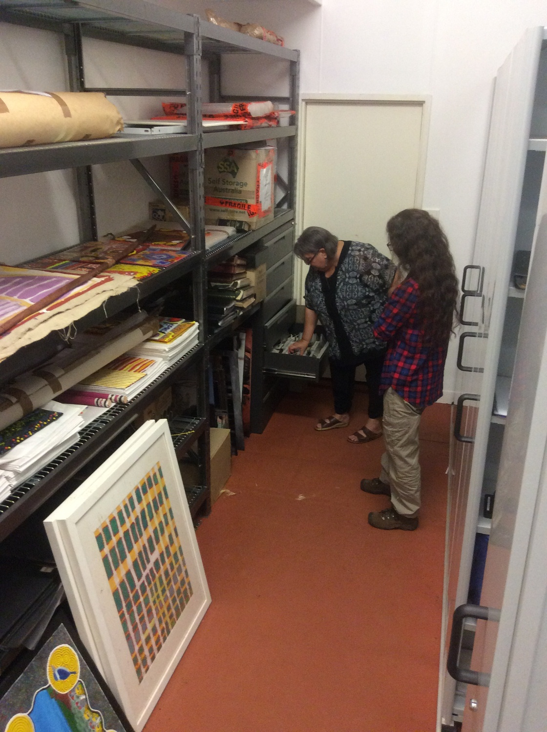 Outgoing Warlayirti Artists manager, Sheryl Anderson showing DRS Indigenous Community Liaison and Project Coordinator, Philippa Jahn artworks, documentation and recordings in the archive. © AGWA 2016