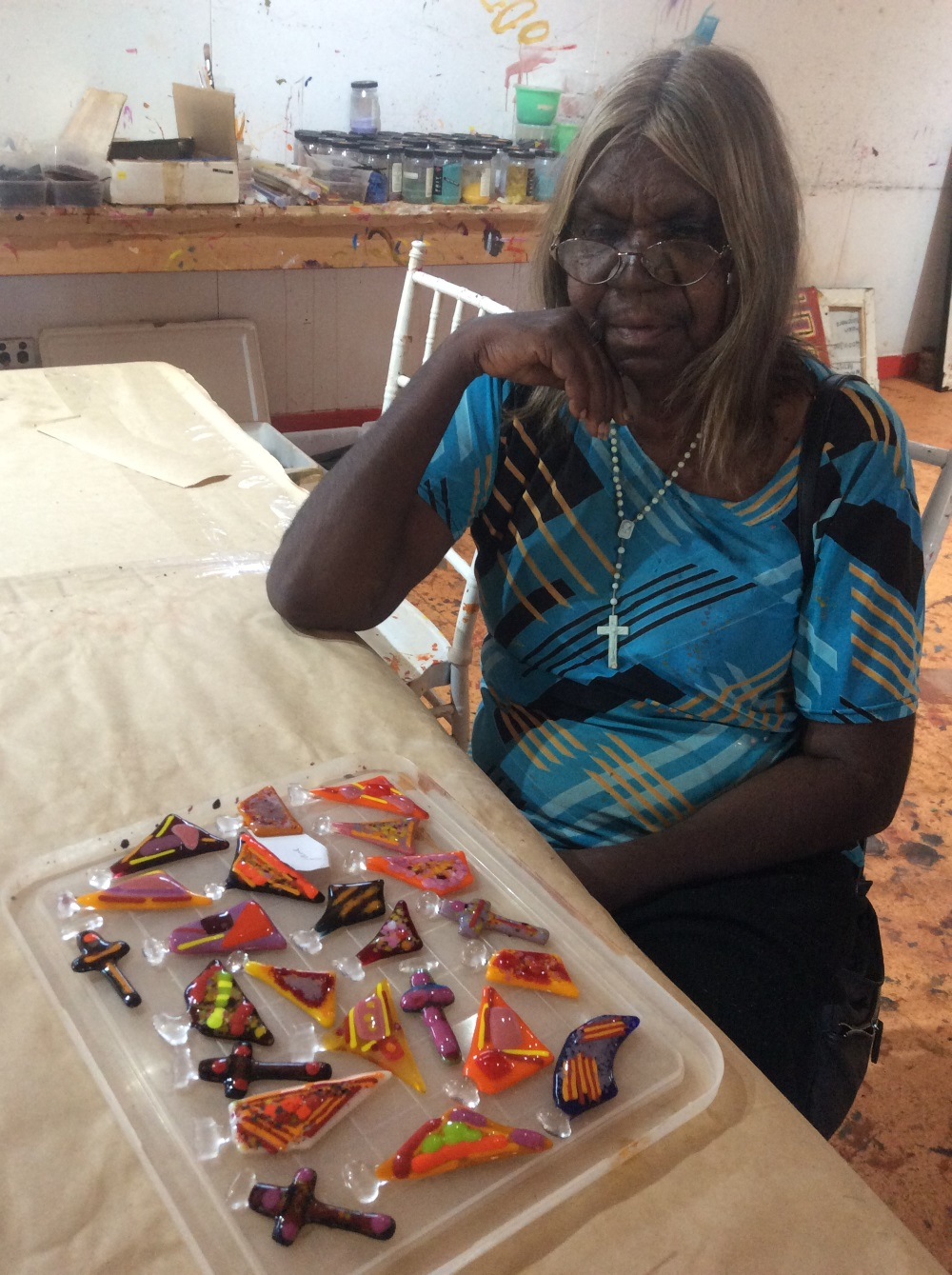 Jane Gimme with jewellery pendants she made during the glass workshop at Warlayirti Artists Art Centre. Balgo, Nov 2017 © AGWA