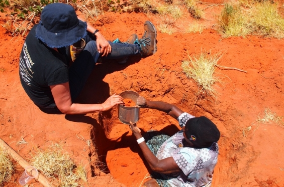 Carly Lane assisting Eva (Joan) Nagomara digging for bush potato during the bush tucker daytrip. Outside Balgo, Nov 2017 © Helen Puckey 2017