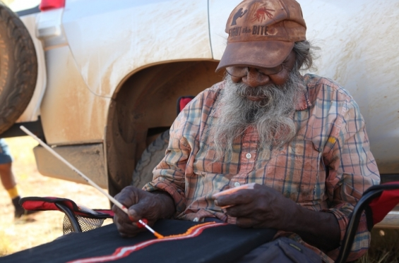 Helicopter Tjungurrayi painting at the shady camp site during the bush tucker daytrip. Balgo, Nov 2017 © AGWA