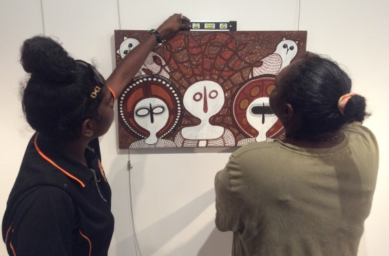DRS Visual Arts Leadership Program participants Cessa Bani and Kirsty Burgu during the 2016 workshop hanging paintings from Mowanjum Art & Culture Centre for the inaugural VALP exhibition. © AGWA
