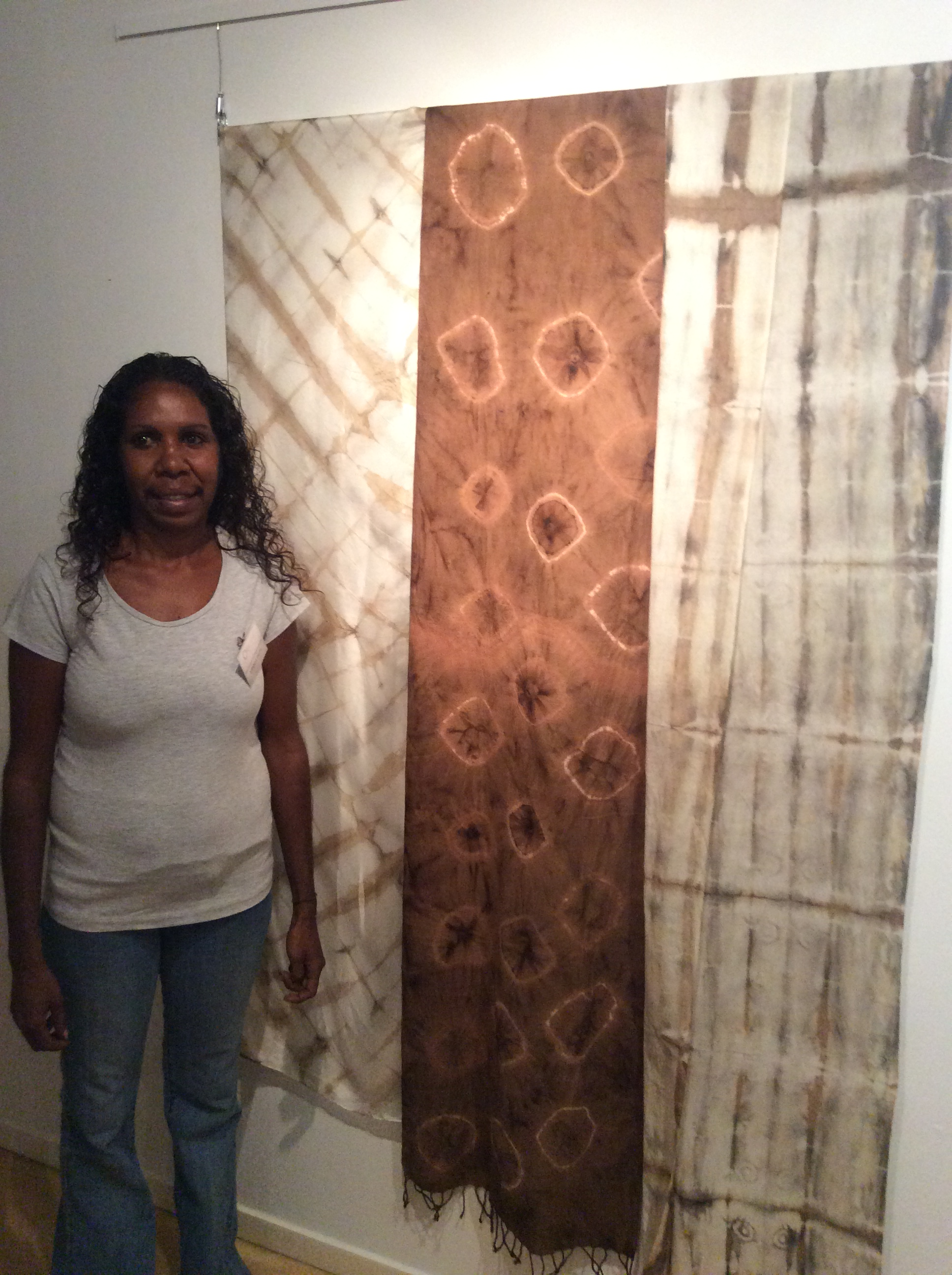 DRS 2016 Visual Arts Leadership Program participant Amanda Smith at the inaugural VALP exhibition opening standing with works from Marnin Studio in Fitzroy Crossing that she helped curate and install. © AGWA